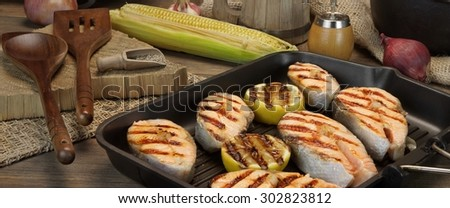 Still Life In The  Rustic Style With Grilled Salmon Steaks On The Rough Wooden Dinning Table - stock photo