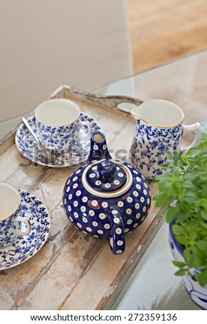 Still life interior design home dining room and kitchen view of a tray with teapot set serving of hot drinking tea in a spacious stylish house. Aspirational home dining room and kitchen, lifestyle. - stock photo