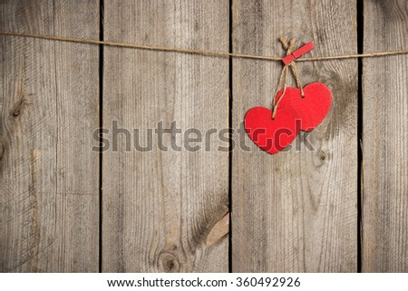 Still life, love and holidays concept. Red heart hanging on the clothesline for Valentine Day. Selective focus, top view, copy space rustic wooden background - stock photo