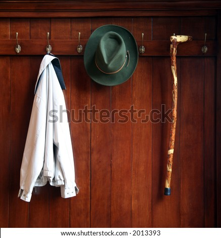 Still life od a wooden clothes rack with a hat,jacket and a cane - stock photo