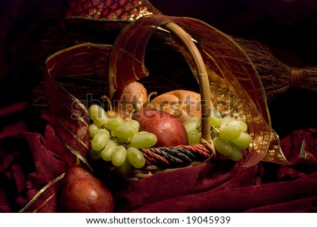 Still life of a basket of bread and fruit against a rich burgundy background, painted with light.