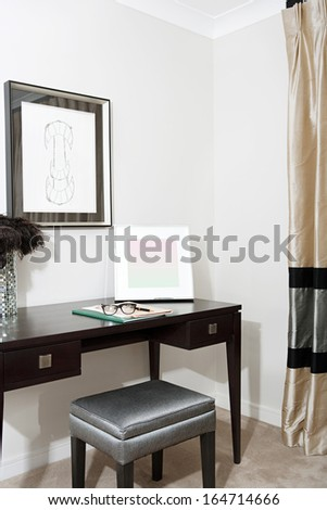 Still life of a bedroom corner with curtains and a writing desk in a luxury hotel room with reading glasses and a pen. Stylish home interior with no people. - stock photo