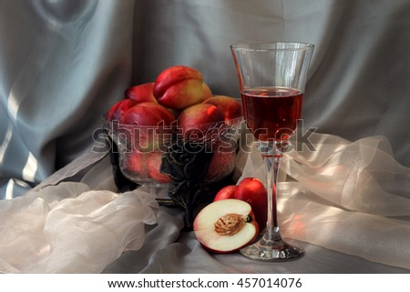 still life of a glass of champagne and nectarines.