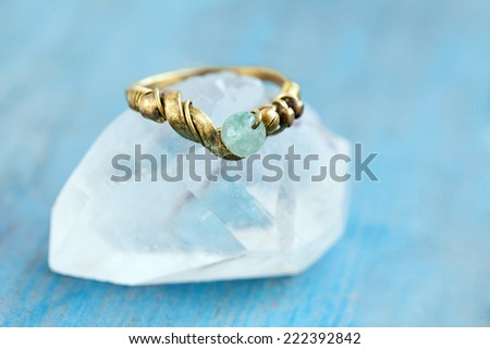 Still life of a hand made tribal ethnic ring resting on a crystal on light blue background. - stock photo