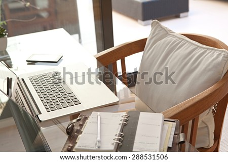 Still life of a home office room with a laptop computer and a smart phone, house interior. Working from home technology in a home work desk, indoors. High technology lifestyle workplace. - stock photo
