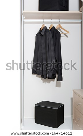 Still life of a professional hotel room wardrobe with a business man tidy black shirts hanging from wooden hangers with a box and draws. Home interior detail with no people. - stock photo