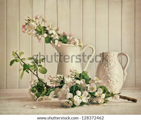 Still life of apple blossom flowers in vase on table - stock photo