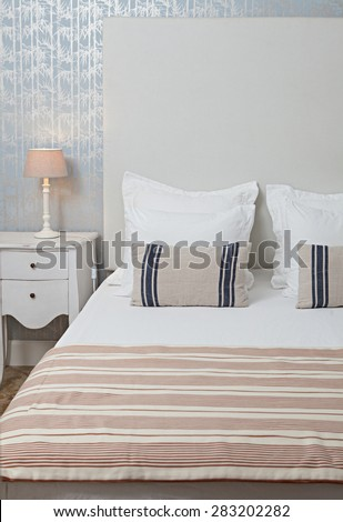 Still life of aspirational luxury home bedroom with stripy furnishings in a quality family home, interior design. Stylish bed with white linen and a pattern wallpaper with bamboo details, indoors. - stock photo