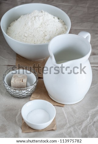 Still life of baking ingredients like flour, milk, yeast and salt. - stock photo