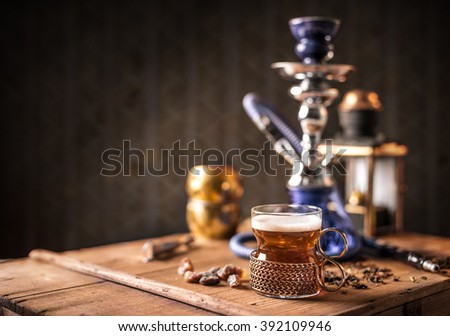 Still life of black tea in glass cup on wooden table, hookah in background - stock photo