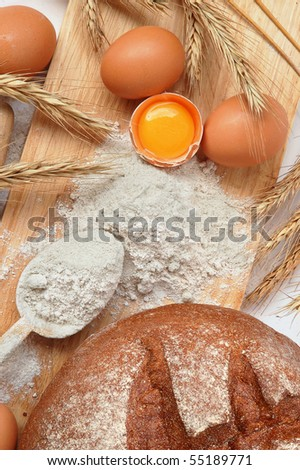 Still life of bread, eggs, cereals, flour and kitchen tools on a wooden board - stock photo