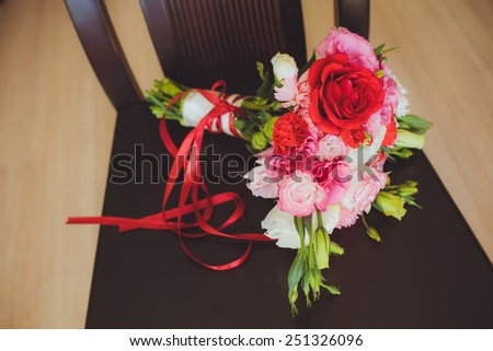 Still Life of Bride's bouquet flowers on brown chair - stock photo