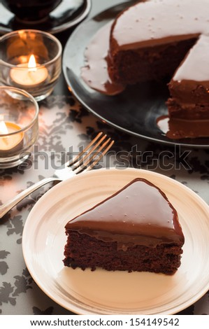 Still life of chocolate cake and candlelight. - stock photo