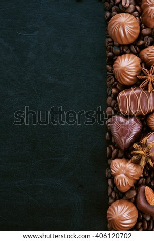 Still life of chocolate coffee beans lying on a dark background - stock photo