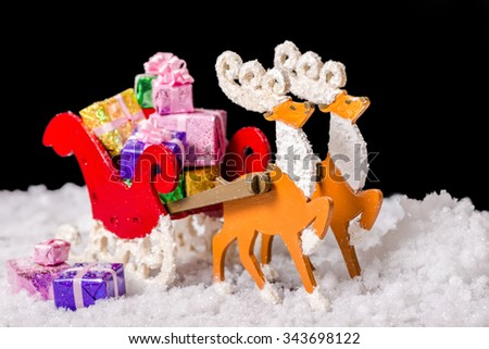 still life of Christmas decoration reindeer and Santa sleigh with gifts in snow is isolated on black background, closeup - stock photo