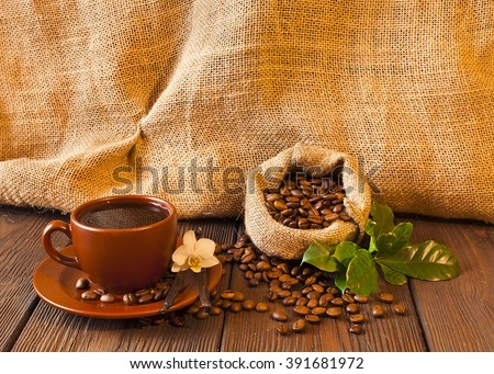 Still life of coffee beans in jute bag with coffee and coffee cup on a wooden table  - stock photo