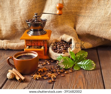 Still life of coffee beans in jute bag with coffee grinder and coffee cup on a wooden table