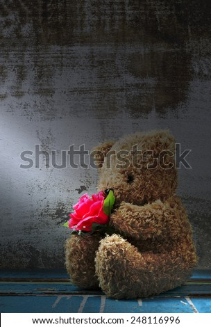 Still life of cute bear doll holding rose bouquet - stock photo