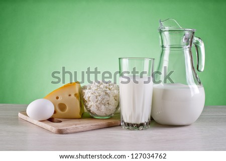 still life of dairy products and cutting boards on a green background - stock photo