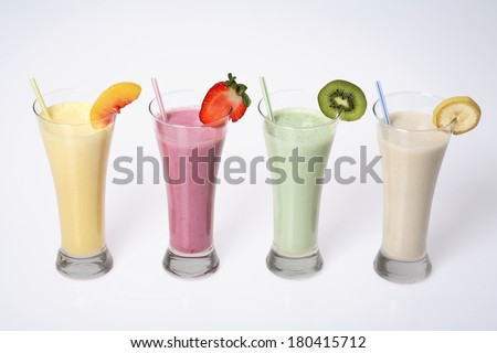 still life of four milkshakes or smoothies in tall glasses  - stock photo