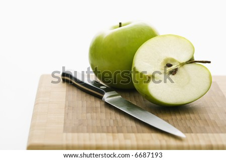 Still life of green apples and knife on cutting board.