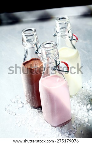 Still Life of Healthy Blended Smoothie Shakes in Three Glass Bottles with Open Tops on Shiny Metal Surface - stock photo