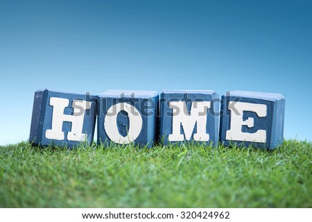 still life of HOME sign concept made of wooden blocks on a green grass under the bright blue sky - stock photo