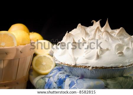 Still life of lemon meringue pie next to basket of lemons on blue print tablecloth - stock photo