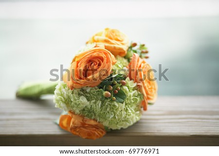 Still life of orange and green wedding bouquet outside - stock photo