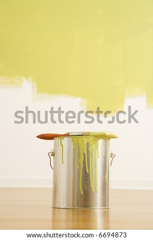 Still life of paintbrush on paint can with painted wall.