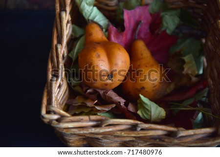 still life of pears in autumn leaves in a wicker basket