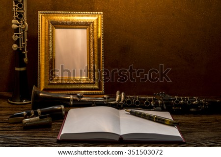 Still life of picture frame on wooden table with clarinet. - stock photo