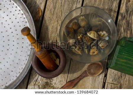 Still life of some of the ingredients and utensils to cook a paella, eg clams, live, in mortar crushed garlic, salt and wooden spoon on a wooden platform - stock photo