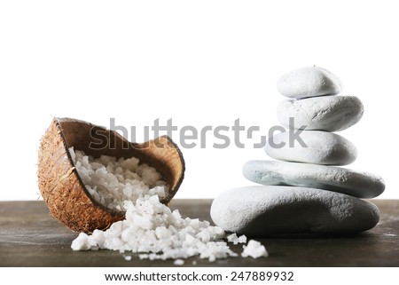 Still life of spa stones and coconut shell of sea salt on wooden surface isolated on white - stock photo