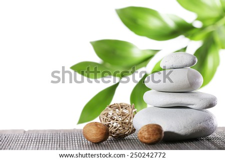 Still life of spa stones on bamboo mat surface with green branch isolated on white - stock photo