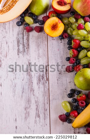 Still life of the different ripe delicious fruits lying on the wooden table - stock photo