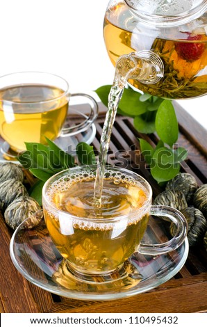 still life of the glass teapot flow green tea in cup on white background, isolated,  tea ceremony - stock photo