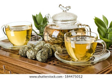 still life of the glass teapot flow green tea in cup on wooden trivet, white background, isolated,  tea ceremony