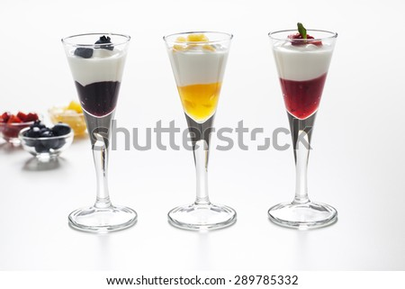 Still life of three cups with yogurt and three kinds of jam (blueberry, peach and strawberry) and decorative toppings of fruits. - stock photo