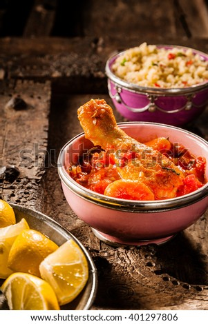 Still Life of Traditional Tajine Food - Individual Serving of Chicken Leg Smothered in Savory Tomato Sauce with Bowl of Couscous and Lemon Wedges Nearby on Rustic Wooden Table - stock photo