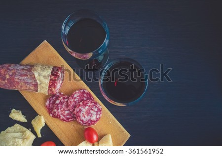 Still life of two wineglasses, salami, tomatoes and pieces of cheese Parmesan on wooden board. Toned image. - stock photo