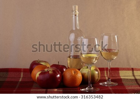 Still life of uncorked transparent glass bottle of semisweet white wine with two filled glasses ripe apples oranges on table covered with red plaid, horizontal photo - stock photo