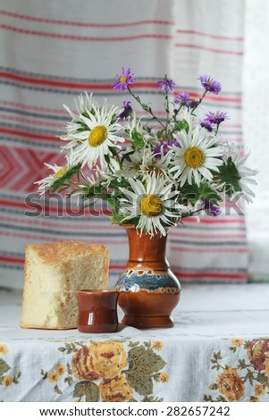 Still life of vase and glass cut lilac and white Aster flowers and slice of yeasted wheat bread - stock photo