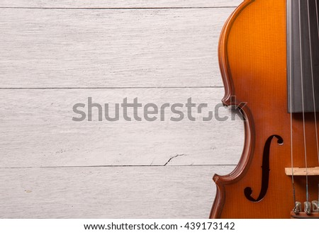 still life of vintage violin on white wooden background - stock photo