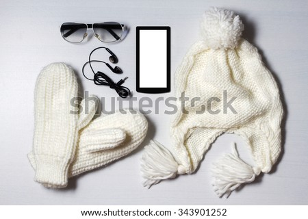still life of winter accessories. white hat, mittens,phone, sunglasses and headphones lie on white wood background. - stock photo