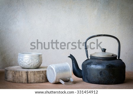 Still life. Old aluminium kettle and cup old thai style retro on wooden background.