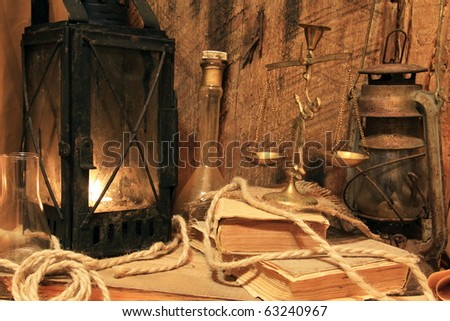 Still life - old lamps, books, balance on wooden background - stock photo