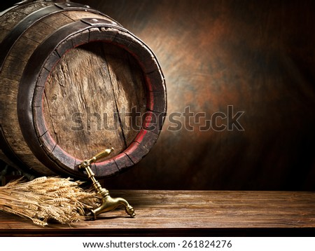 Still life: old wooden pin of beer and wheat on the table in the cellar. - stock photo