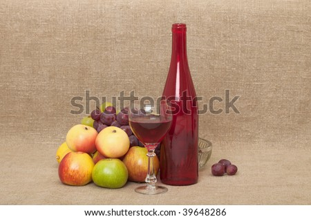 Still-life on a canvas - a red glass large bottle, a glass, apples and grapes - stock photo