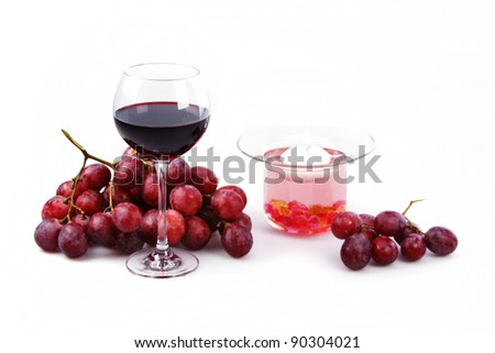 Still life on a white background glass of red wine, grapes and a candle in a decorative candlestick. wine, red, still life, glass, white, background, beautiful, romantic, grapes, candle - stock photo